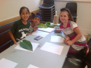 Jessica Spirak demonstrates the art of making leaf rubbings to Simaren and Devinder Serai.